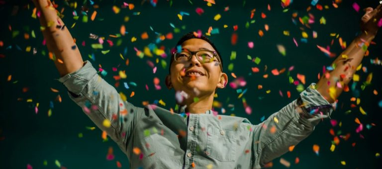 man in green shirt celebrating with confetti